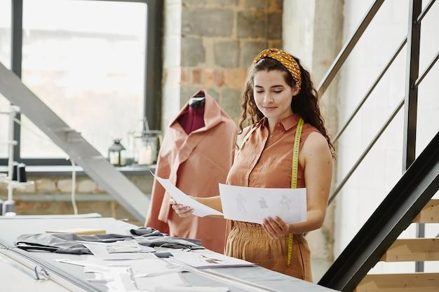 Młoda ładna projektantka mody przygląda się szkicom nowych modeli do sezonowej kolekcji i wybiera część z nich do szycia