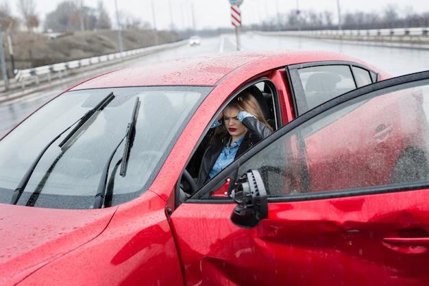 Młoda ładna przestraszona kobieta w samochodzie. ranna kobieta czuje się źle po wypadku samochodowym