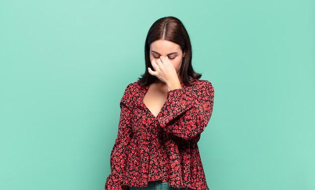 Młoda ładna przypadkowa kobieta czuje się zestresowana, nieszczęśliwa i sfrustrowana, dotyka czoła i cierpi na migrenę z silnym bólem głowy