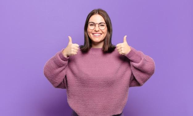 Młoda ładna przypadkowa kobieta, szeroko uśmiechnięta, szczęśliwa, pozytywna, pewna siebie i odnosząca sukcesy, z dwoma kciukami do góry