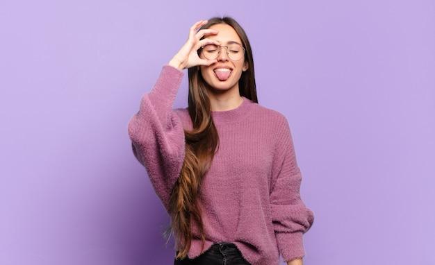 Młoda ładna przypadkowa kobieta uśmiecha się radośnie z zabawną miną, żartuje i patrzy przez wizjer, szpiegując sekrety