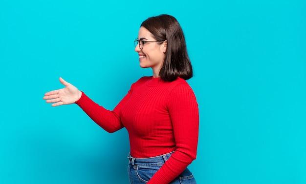 Młoda ładna przypadkowa kobieta uśmiecha się, wita cię i oferuje uścisk dłoni, aby zamknąć udaną umowę, koncepcja współpracy