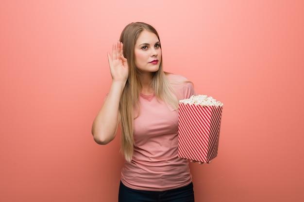 Młoda ładna rosjanka próbuje słuchać plotek. trzyma popcorns.