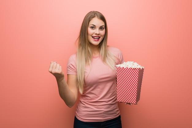 Młoda ładna rosjanka zaskoczona i zszokowana. trzyma popcorns.