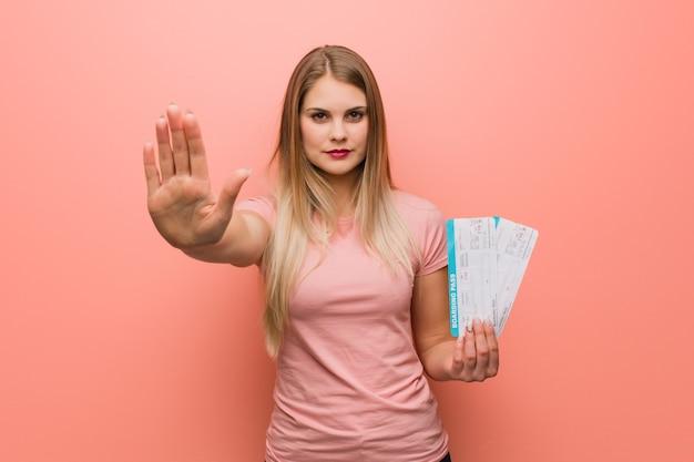 Młoda ładna rosyjska dziewczyna kładzie rękę z przodu. trzyma bilety lotnicze.