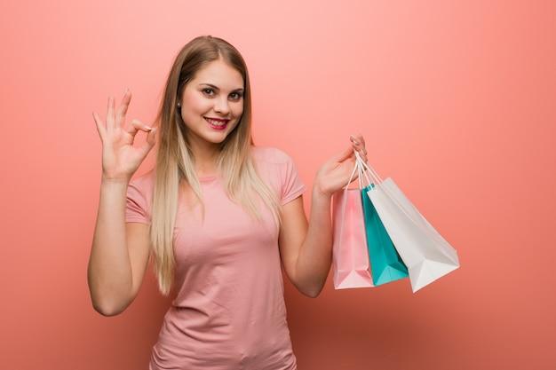 Młoda ładna rosyjska dziewczyna rozochocony i ufny robi ok gestowi. trzyma torby na zakupy.