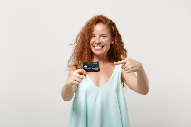 Młoda ładna ruda kobieta dziewczyna w dorywczo lekkie ubrania pozowanie na białym tle na białym tle, portret studio. koncepcja życia ludzi. makieta miejsca na kopię. wskazując palcem wskazującym na kredytowej karty bankowej.