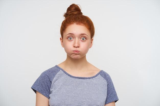 Młoda ładna ruda kobieta z kok fryzurą na białym tle