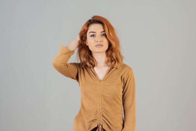 Młoda ładna ruda na szaro trzymająca rękę na jej włosach.