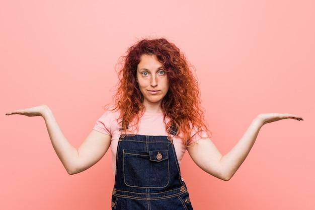 Młoda ładna rudowłosa kobieta ubrana w jeansowe spodnie ogrodniczki sprawia, że waga jest w rękach, jest szczęśliwa i pewna siebie.