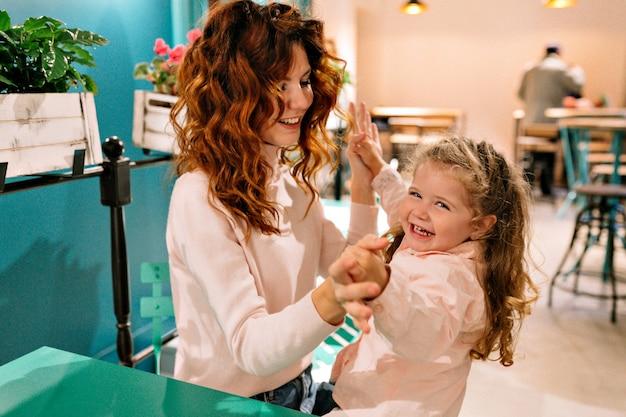 Młoda ładna rudowłosa mama ze swoim małym uroczym kręconym dzieckiem spędza weekend w rodzinie