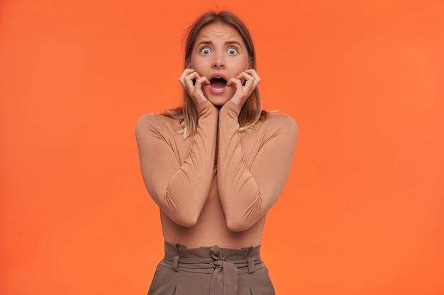 Młoda, ładna siwowłosa kobieta z otwartymi oczami z przypadkową fryzurą, trzymająca dłonie na policzkach i wykrzywiona twarz, patrząc przerażony z przodu, pozująca nad pomarańczową ścianą