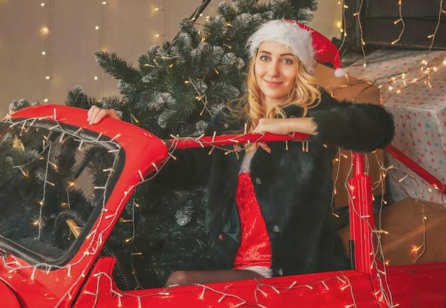 Młoda ładna śnieżna dziewczyna na świątecznych dekoracjach i czerwonym samochodzie z prezentami i choinką