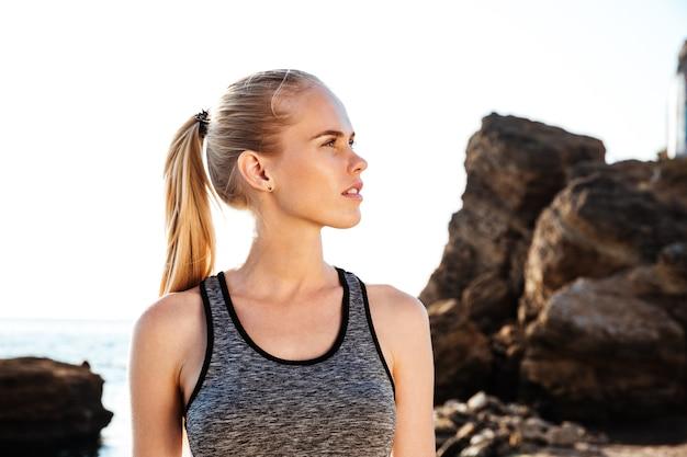Młoda ładna sportowa kobieta odpoczywa po treningu na plaży o zachodzie słońca