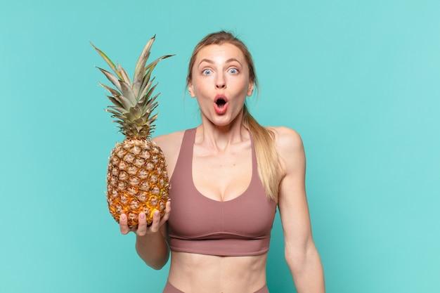 Młoda ładna sportowa kobieta przestraszona wyrazem twarzy i trzymająca ananasa