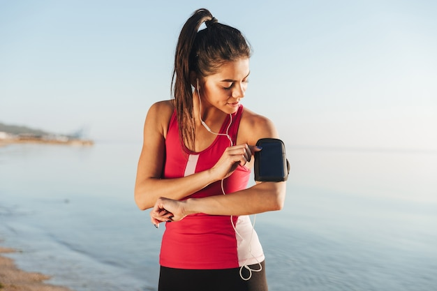 Młoda ładna sportowa kobieta przygotowuje się do biegania podczas korzystania ze smartfona