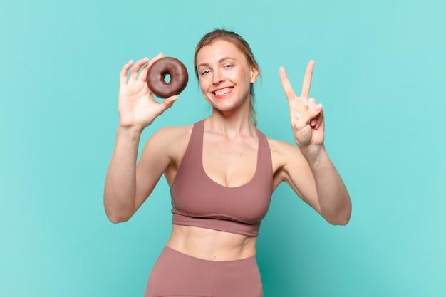 Młoda ładna sportowa kobieta świętująca zwycięstwo i trzymająca pączka