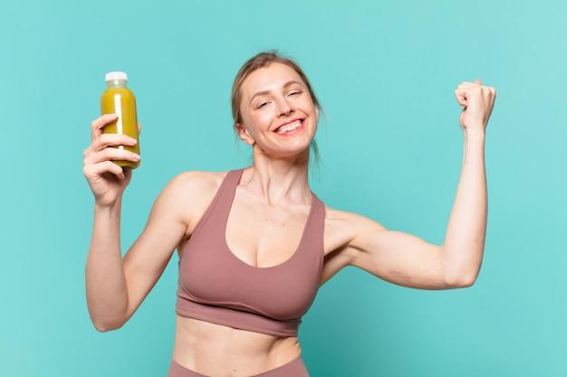 Młoda ładna sportowa kobieta świętująca zwycięstwo i trzymająca smoothy