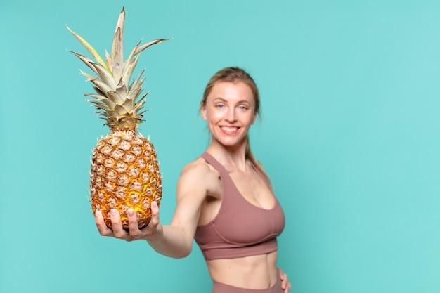 Młoda ładna sportowa kobieta szczęśliwa ekspresja i trzymająca ananasa