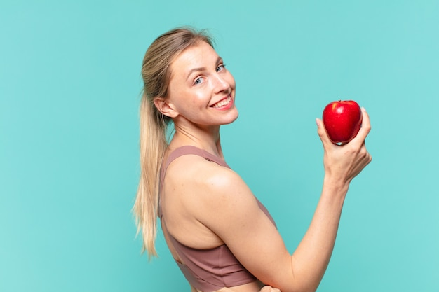 Młoda ładna sportowa kobieta szczęśliwa ekspresja i trzymająca jabłko