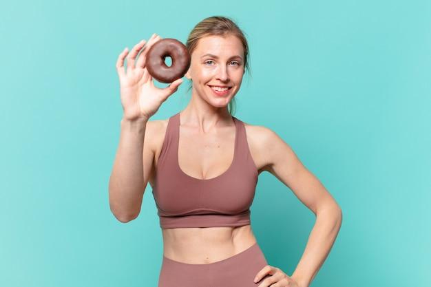 Młoda ładna sportowa kobieta szczęśliwa ekspresja i trzymająca pączka