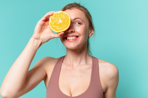 Młoda ładna sportowa kobieta szczęśliwa ekspresja i trzymająca pomarańczę