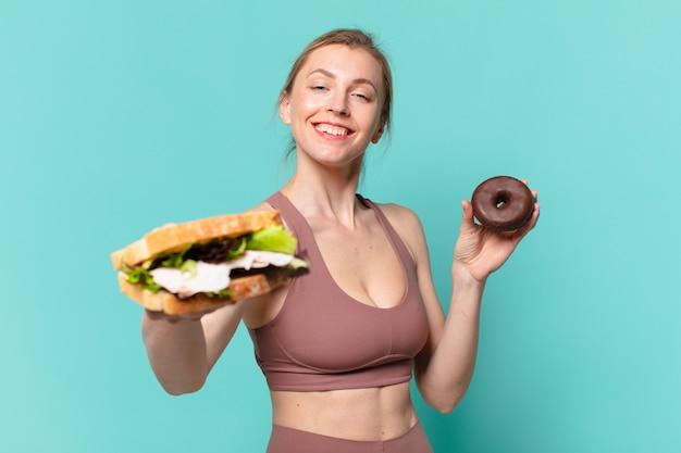 Młoda ładna sportowa kobieta szczęśliwa wypowiedzi i trzymająca kanapkę i pączek