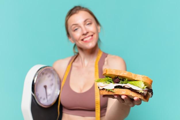 Młoda ładna sportowa kobieta szczęśliwa wypowiedzi i trzymająca wagę i kanapkę