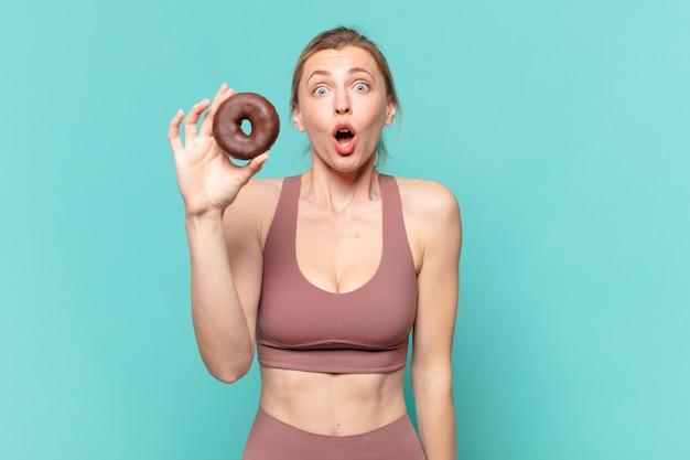 Młoda ładna sportowa kobieta zaskoczona wyrazem twarzy i trzymająca pączka
