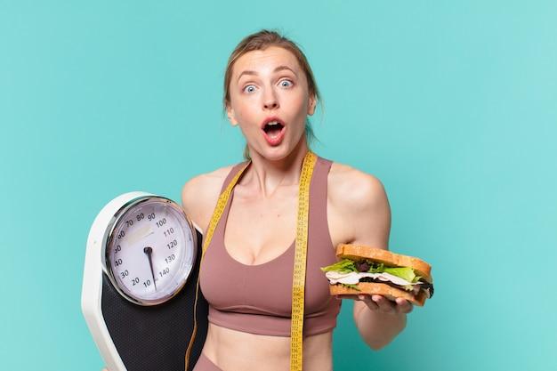 Młoda ładna sportowa kobieta zaskoczyła wyrazem twarzy i trzyma wagę i kanapkę