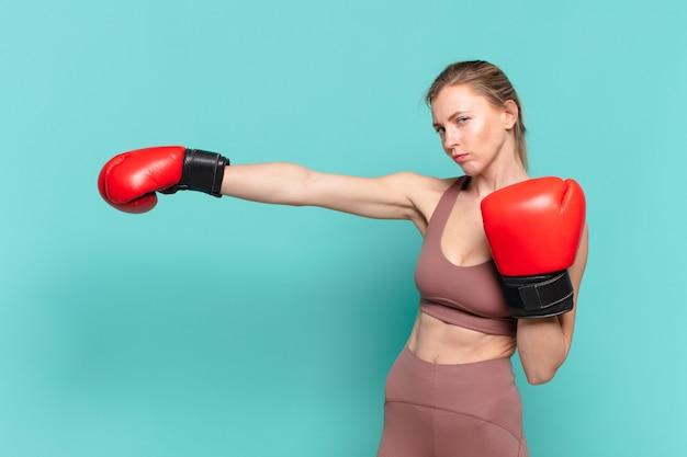 Młoda ładna sportowa kobieta zły wyraz twarzy i boks
