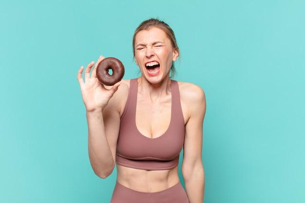 Młoda ładna sportowa kobieta zły wyraz twarzy i trzymająca pączka