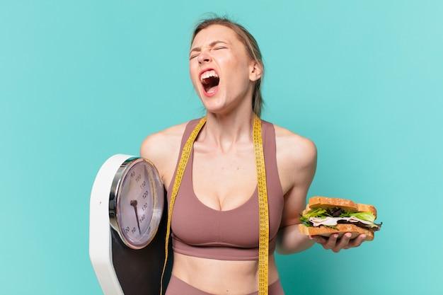 Młoda ładna sportowa kobieta zły wyraz twarzy i trzymająca wagę i kanapkę