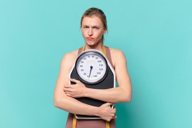 Młoda ładna sportowa kobieta zły wyraz twarzy i trzymająca wagę