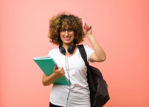 Młoda ładna studencka kobieta ono uśmiecha się radośnie i szczęśliwie, wskazujący w górę z jedną ręką kopiować przestrzeń przeciw menchii ścianie