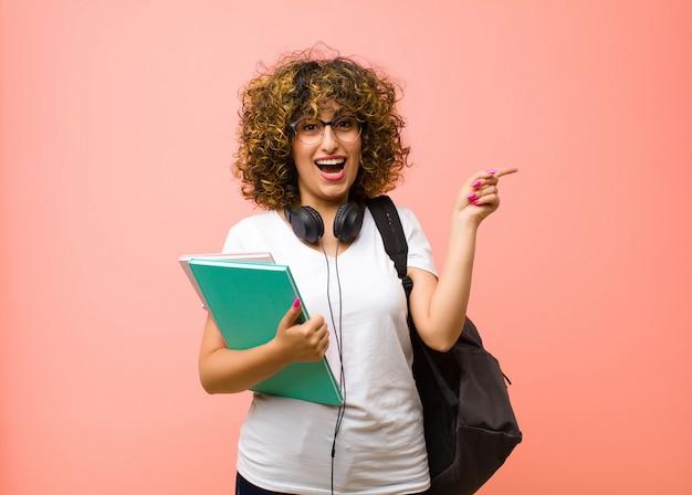 Młoda ładna studencka kobieta śmieje się, wygląda na szczęśliwą, pozytywną i zaskoczoną, realizując świetny pomysł wskazujący na boczną przestrzeń kopii na różowej ścianie