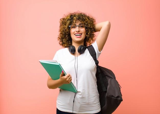 Młoda ładna studencka kobieta wyglądająca na szczęśliwą, beztroską, przyjazną i zrelaksowaną, cieszącą się życiem i sukcesem, z pozytywnym nastawieniem ponad różową ścianą