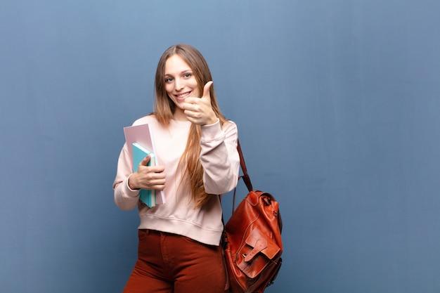 Młoda ładna studencka kobieta z książkami i torbą przeciw błękit ścianie z copyspace