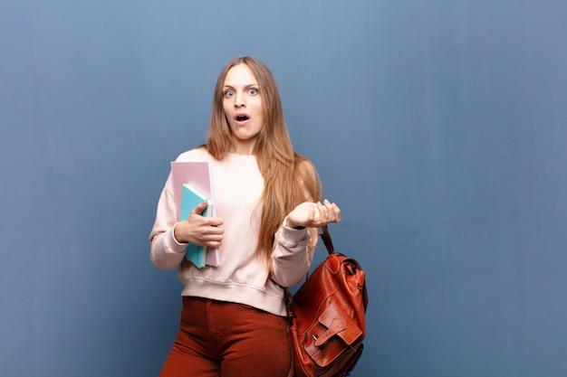Młoda ładna studencka kobieta z książkami i torbą przeciw błękit ścianie z odbitkową przestrzenią