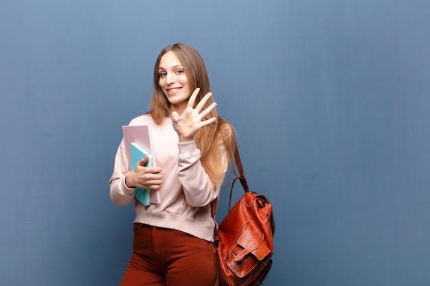 Młoda ładna studencka kobieta z książkami i torbą