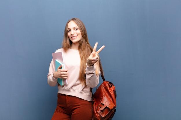 Młoda ładna studencka kobieta z książkami i torby błękita ścianą z copyspace