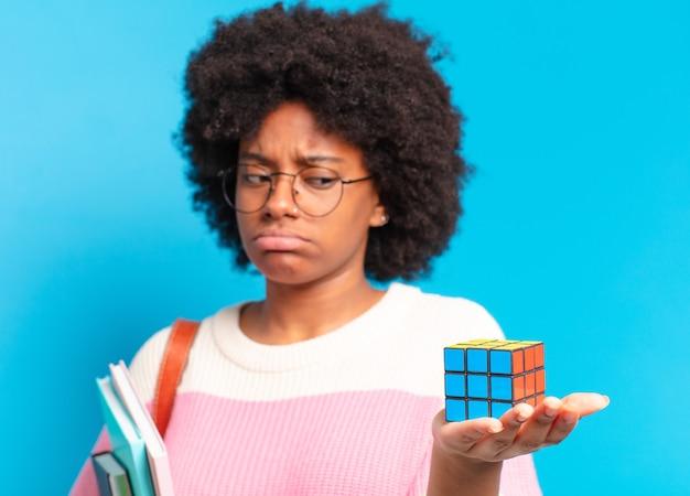 Młoda ładna studentka afro próbuje rozwiązać problem z inteligencją