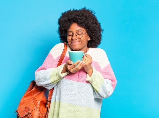 Młoda ładna studentka afro z filiżanką kawy