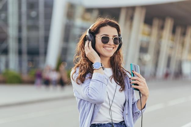 Młoda ładna studentka czeka na taksówkę i słucha muzyki