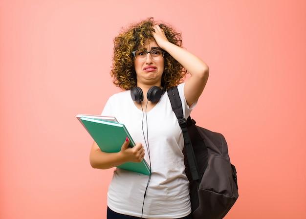 Młoda ładna studentka czująca się sfrustrowana i zirytowana, chora i zmęczona porażką, zmęczona nudnymi, nudnymi zadaniami na różowej ścianie