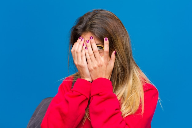 Młoda ładna studentka czuje się przestraszona, zerkając lub szpiegując oczy na wpół pokryte rękami