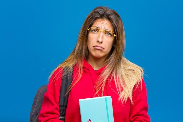 Młoda ładna studentka czuje się smutna i płaczliwa z nieszczęśliwym spojrzeniem, płacze z negatywnym i sfrustrowanym nastawieniem