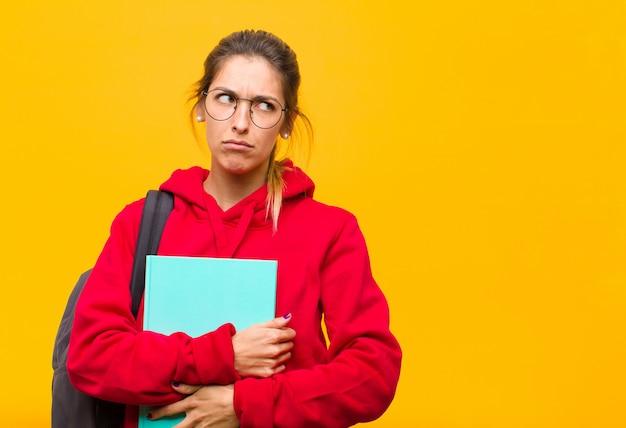 Młoda ładna studentka czuje się smutna, zdenerwowana lub zła i patrzy w bok z negatywnym nastawieniem, marszcząc brwi w sporze