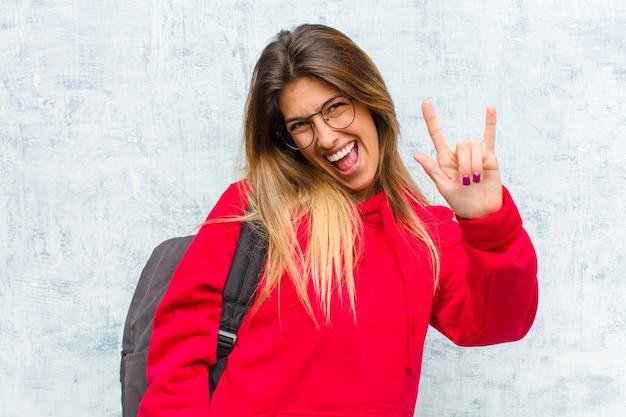 Młoda ładna studentka czuje się szczęśliwa, zabawna, pewna siebie, pozytywna i zbuntowana, wykonując ręką znak rockowy lub heavy metalowy