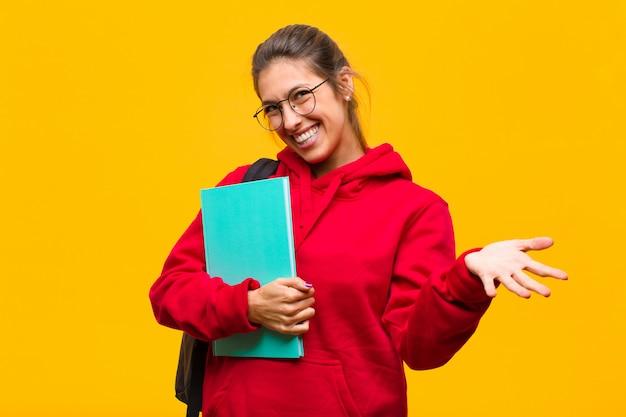 Młoda ładna studentka czuje się szczęśliwa, zdziwiona, szczęśliwa i zaskoczona, jak mówienie poważnie